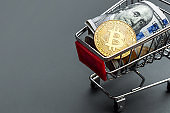 Shopping cart with dollar bills and coin of bitcoin. Business concept.