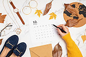 Flat lay with calendar for october with woman fashion fall accessories. Social media blog, schedule, planning, autumn concept. Flatlay, top view