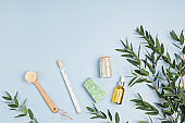 Cosmetics branding mockup. Bottles of essential oil, sea salt, soap bar, fresh eucalyptus branches on blue background. Natual organic ingredients for skin care, body treatment, beauty product concept