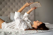 Rest, comfort, leisure and people concept. Sexy woman reading book in bed at home