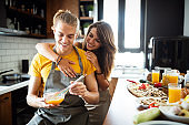 Happy young couple have fun in modern kitchen while preparing fresh food