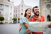 Summer holidays, dating and tourism concept. Smiling couple walking with map in the city
