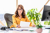 Middle aged businesswoman sitting behind her computer while working from home