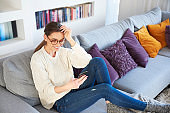 Young woman using her mobile phone and text messaging at home
