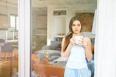 Young woman drinking her morning tea and daydreaming while looking through the window