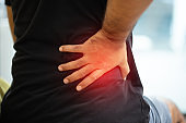 A man is suffering from back pain. He took his own hand to massage the back of the pain area.