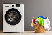 Piles of laundry in the basket and the washing machine are placed close to each other.