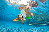 Happy family dive underwater with fun in swimming pool