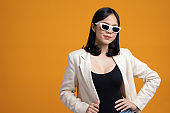 Attractive Beautiful asian woman standing and posing. Sexy female in suit wearing sunglasses on isolated yellow background.