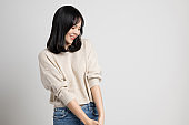 Beautiful young asian woman smiling and happy. Charming female standing on isolated white background.