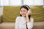 Relaxing time on sofa. Beautiful young asian woman lay down on sofa and listening to the music with headphone. She has rhythm Lifestyle in living room at house in the morning.
