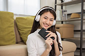 Relaxing time in living room. Beautiful young asian woman choose music from smartphone take a rest and listening song with headphone and dancing. Lifestyle in living room at house in the morning.