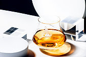 Whiskey, scotch or bourbon glass with ice on black and white background with geometric cubes and circles. Contemporary still life