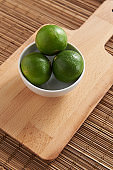 Three lemons are placed on a cutting board, a mat on the table.
