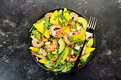 Shrimps, Mango and Avocado Salad with Walnut, Spinach and Arugula. Healthy Eating food concept Top view, gray background