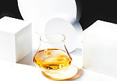 Contemporary still life with whiskey, scotch or bourbon in glass with shard ice on black white background with geometric cubes and circles