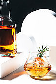 Whiskey, scotch or bourbon glass with rosemary, shard ice on black white background with geometric cubes and circles. Contemporary still life