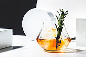 Contemporary still life with whiskey, scotch or bourbon glass with rosemary, shard ice on black white background with geometric cubes and circles