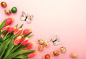 Spring Easter holiday pink background with tulips, quail eggs, butterflies. Top view banner