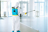 A disinfector in a protective suit and mask sprays disinfectants in  office.