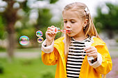 Cute little  girl in the autumn on a walk blowing soap bubbles.