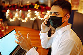 Young man in protective face mask speaks on the phone at home during working on laptop. Self-isolation.