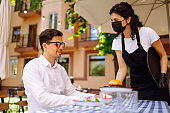 Young waitress in a protective medical mask and gloves with ordered meals serves food at table outside