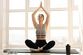 Sports woman practicing yoga on fitness mat