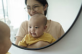 Cheerful smiling Asian mother and little newborn baby son having fun playing and looking at their faces in mirror at home.