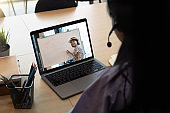 Asian young girl student learning virtual internet online class from school teacher by remote meeting due to covid pandemic. Female teaching by using headphone and whiteboard