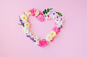 Beautiful heart shaped,Frame composition,various fresh flowers on pink background.Copy space.Valentines, mothers,women's day concept.Flat lay,top view.Template,design of wedding invitations,cards
