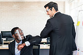 Caucasian and African Businessman wearing a face shield and greeting by elbow bump instead of shaking hands in a business meeting during coronavirus epidemic.