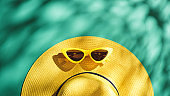 Yellow straw hat and sunglasses over green turquoise background with sunlight and tree shadow ,Minimal summer beach sea