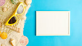 summer sunlight concept.white blank picture frame on sand with beach accessory on blue sea background