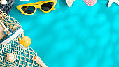 sunny day summer beach sea accessories,sunglasses,brown hat and seashell over blue background banner with sunlight