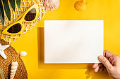 hand holding paper card on yellow summer hard light with beach accessories.mock up for display of design in summer concept