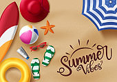 Summer beach vector banner design. Summer vibes text in beach sand background with realistic beach elements like surfboard, flip flop, beach ball, sunglasses, umbrella and lifebuoy.