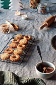 Christmas Linzer cookies filled on cooling rack, metal plate. Sandwich cookies filled with hazelnut spread, nougat cream. Hand holds cookie. Xmas trees and candles on beige linen tablecloth