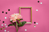 Pink peony flower, greeting card, golden frame. Minimal simple flat lay on abstract pink geometric background with paper confetti, polka dots