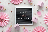 Text Happy Birthday on letter board, letterboard. Creative flat lay, top view on ivory, off white textile. Party decor, paper fans, gift boxes, hearts. Natural pink hyacinth flowers, perfume