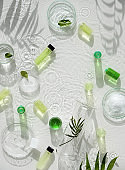 Cosmetic skincare background. Herbal medicine with green leaves. Natural sunlight, long shadows. Splashes of water, splashes. Chemical glassware, petri dishes, vials. Natural body care concept