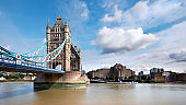 Tower Bridge on a bright sunny day with blue sky and clouds. Calm water with reflections. London, England, UK