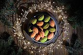 Walnut shaped cookies with Dulce De Leche. Tasty dessert on dark background with natural Xmas decor. Fir twigs on dark rustic wood. Festive lights, garland in circle around the plate