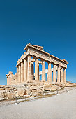 Parthenon temple on a bright day with blue sky and clouds. Panoramic image of ancient buildings in Acropolis hill in Athens, Greece. Classical ancient Greek civilization landmark, travel background