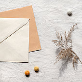 Square textile flat lay with card, envelope, dry reeds, pampas grass. Off white cotton tablecloth background with knitted cotton balls. Simple minimal arrangement, natural light