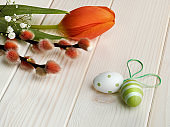 Easter eggs, pussy willow and red tulip on off white wooden table. Close-up on Springtime flowers and decor. Spring greeting card in red, green and cream white colors