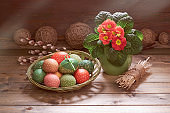 Red orange primrose flowers in the pot. Easter eggs and pussy willow twigs. Springtime decorations on rustic wooden background. Retro toned image of rustic Easter decor. Sunlight with shadows