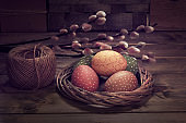 Painted Easter eggs in wattle rattan wreath nest. Hemp cord and bunch of pussy willow twigs. Vintage rustic interior, arrangement on dark rustic wooden table. Retro toned image