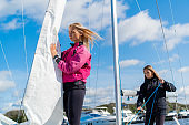 On the pier, two pretty girls pull sails on a boat to participate in a sailing competition