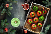Marzipan sponge apples. Christmas dessert with cup of tea, fir twigs, green candle, pine cone, soft star. Top view on in rustic wooden tray on textile towel